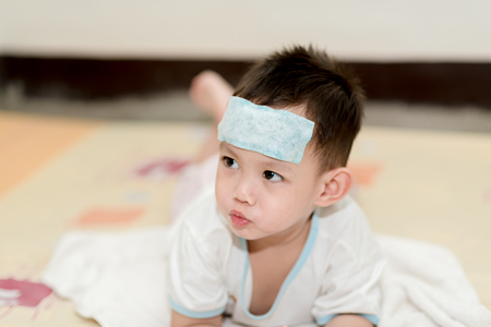 Asian boy having fever . The kid attach cooling gel pad on his forehead for relief fever