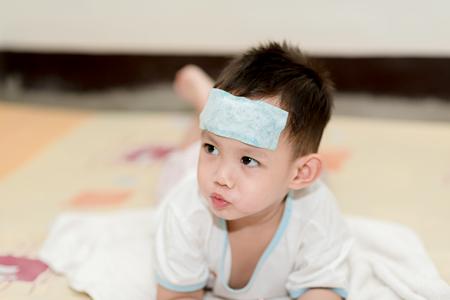 El muchacho asiático que tiene fiebre. El chico adjuntar refrigeración almohadilla de gel en su frente para la fiebre alivio Foto de archivo - 74337656