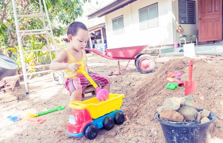 Bebé tailandesa palying en la pila de arena con el juguete y un tenedor de plástico, cuchara, camión, carretilla de rueda Foto de archivo - 74413477
