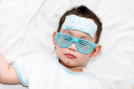 El muchacho asiático que tiene fiebre. El chico adjuntar refrigeración almohadilla de gel en su frente para la fiebre alivio Foto de archivo - 74413479