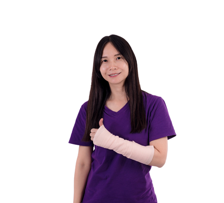 Asian lady in purple T shirt wearing  elastic bandage on her arm.With clipping path