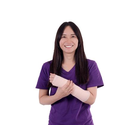 Señora asiática en camiseta púrpura con vendaje elástico en su brazo. Con trazado de recorte Foto de archivo - 87102907