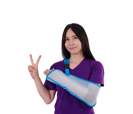 Asian lady in purple T shirt wearing arm sling . Her arm swathe  by elastic bandage. with clipping path