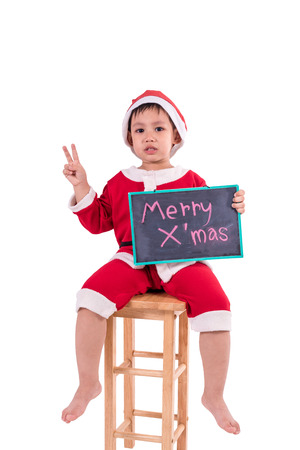 Asian kid dress up as santa claus. In his hand holding the black board . Isolated with clipping path