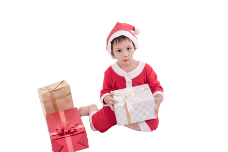 Asian kid dress up as santa claus with gift boxes .