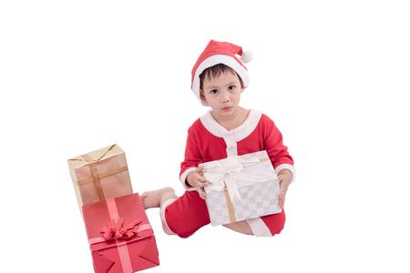 El niño asiático se viste como Papá Noel con las cajas de regalo. Foto de archivo - 90935869