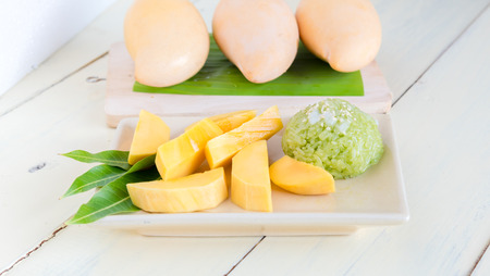 Thai style tropical dessert, sticky rice mixed coconut milk  with mango Foto de archivo - 111370730