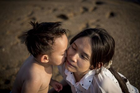 Asian boy kissing mother in nature Stock Photo