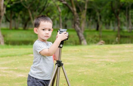 Asian baby boy taking photo graphy in nature by DSLR camera and tripods Stock Photo