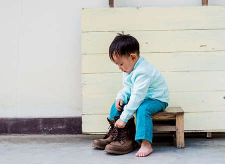 Asian baby boy try to wearing father boots