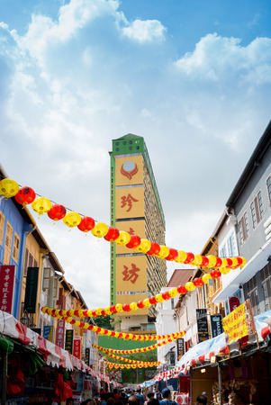 notable: SINGAPORE - MAY 06, 2016: Chinatown with notable Chinese buildings, restaurants and decoration. Many tourists find there authentic food, clothes and other stuff and people engaging in daily activity.