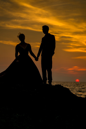 prewedding: Silhouette couples taking a photo prewedding before sunset on the beach rock , Phuket Thailand.