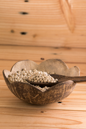 carminative: Close-up shot pepper with wood spoon on wooden background