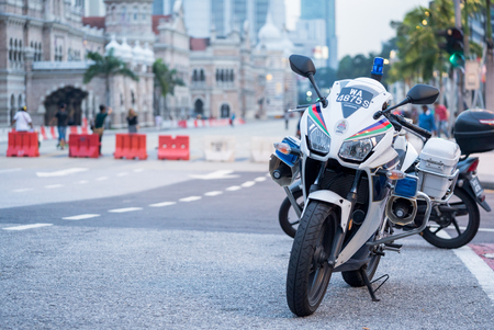 questioned: Kuala Lumpur, MALAYSIA  May 20 2016 - Police motorcycles on a city sidewalk prepare to leave after several officers questioned a man.