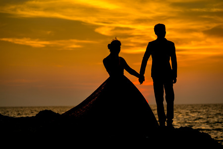 prewedding: Silhouette couples taking a photo prewedding before sunset on the beach rock , Phuket Thailand.