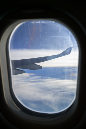 through window: Clouds and sky as seen through window of an aircraft