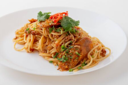 Spicy Spaghetti with Thai sausage on wood table.