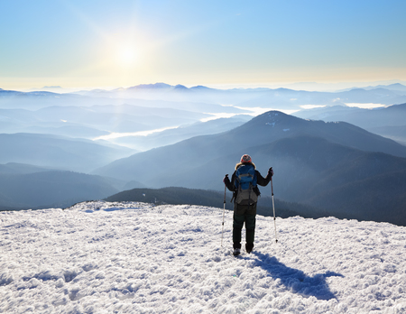 A tourist girl is going towards the sun ang high mountains covered with fog on the frosty winter morning