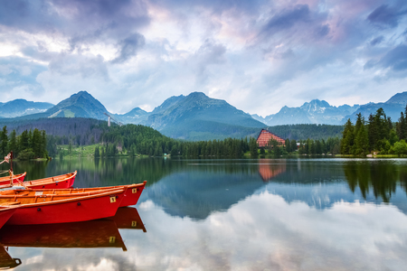 The picture captures the view of a person watching boats reverie, calm lake, fantastic mountains and the clouds floating across the sky
