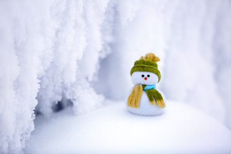 Incredible, beautiful, interesting white snow froze in strange textures, forms and snowflakes, and among all this beauty there is a little snowman in a hat and scarf. Stock Photo