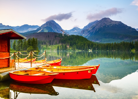 Red boats moored at wooden house on a lake with a clear  water against the background of high mountains.Strbske Pleso lake, Slovakia, Tatra mountains Stock Photo