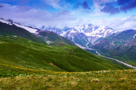 From the lawn with flowers opens a panoramic view of the broad river, rocky mountains in the snow, green meadows and cloudy sky. Upper Svaneti, Georgia, Europe. Happy lifestyle. Beautiful universe.