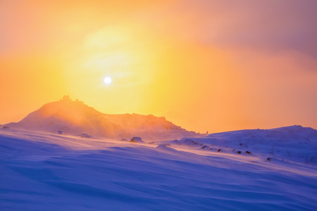 christmas grounds: Sunrise enlightens sky, mountain and trees standing in snowdrifts covered by frozen snow with yellow shine. Stock Photo