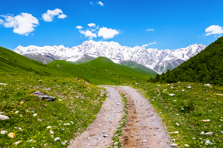 From the broad road with stones can be seen extremely picturesque green hills and snow-covered rocky Shkhara mountain. Upper Svaneti, Georgia, Europe. Happy lifestyle. Beautiful universe.