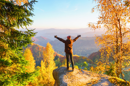 The tourist girl is staying on the edge of gray stone with  hands spread aside watching on the sun rising, autumn forest and landscapes.