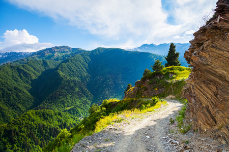 a wonderful world: A wide road with a cliff leads down to the high Caucasus mountains covered with green forests on a sunny summer day. Upper Svaneti, Georgia, Europe. Happy lifestyle. Beautiful universe. Stock Photo