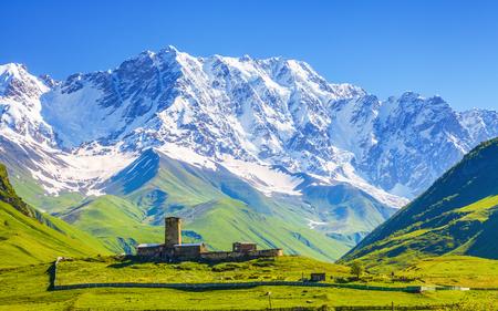 a wonderful world: View on Ushguli village at the foot of snow-capped Mt. Shkhara. Location place Lamaria Church Jgrag, Upper Svaneti, Georgia, Europe.