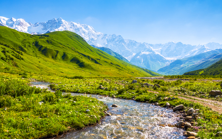 a wonderful world: Beautiful mountain stream with colorful stones on the shore stretched among large mountains and forests. Upper Svaneti, Georgia, Europe. Happy lifestyle. Beautiful universe.