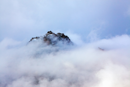 The tops of rugged mountains in the fog.