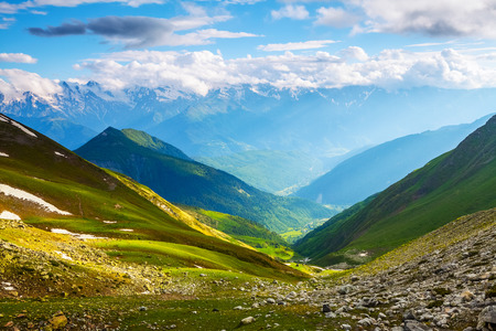 a wonderful world: On the meadow shines a nice sunbeam, all around are the green hills, rocky mountains and cloudy sky.