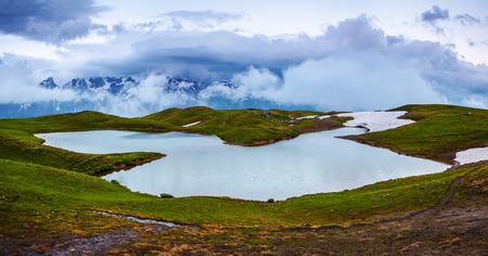 a wonderful world: High mountain lake, rocky mountains and fog.