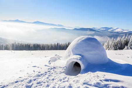 Maravillosa enorme cabaña nevada blanca, iglú la casa de turista aislado está de pie en la alta montaña lejos del ojo humano Foto de archivo