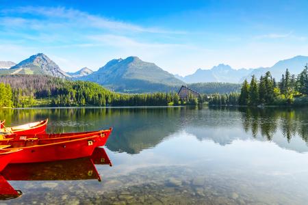 snění: Obrázek zachycuje pohled na člověka, který sleduje plavbu na lodi, klidné jezero, fantastické hory a mraky plovoucí po obloze Reklamní fotografie