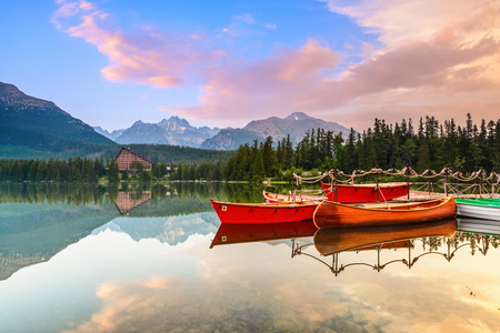 Beautiful high mountains around the incredibly magic lake with red boats and canoe on a spring day.Strbske Pleso lake, Slovakia, Tatra mountains. Stock Photo