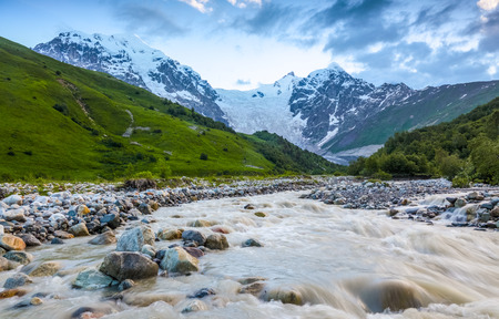 steep: From the river shore, covered with stones, opens view on fantastic glacier and steep rocky mountains with green meadows, which are covered with snow.Happy lifestyle.