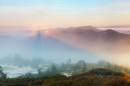wanderlust: From the lawn with orange grass opens a panorama of high mountains, blue sky with clouds and a Brocken Spectre in the fog on an autumn day.
