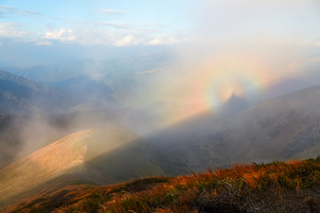 spectre: From the lawn with orange grass opens a panorama of high mountains, blue sky with clouds and a Brocken Spectre in the fog on an autumn day.