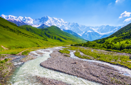 a wonderful world: From the river shore, covered with stones, opens view on fantastic glacier and steep rocky mountains with green meadows, which are covered with snow.Happy lifestyle.
