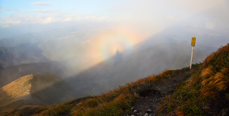 spectre: From the trail with the safety sign �Beware� open fantastic views of the mountains and the colorful phenomenon Brocken Spectre on a foggy morning. Stock Photo