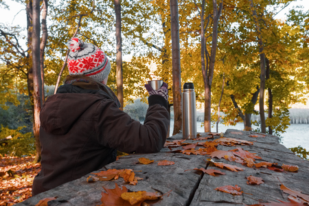 calendario noviembre: The girl in hat and jacket is sitting at the wooden table and drink king tea on the bank of the lake in sunny autumn day.
