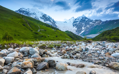 From the river shore, covered with stones, opens view on fantastic glacier and steep rocky mountains with green meadows, which are covered with snow.Happy lifestyle. Beautiful universe. Stock Photo