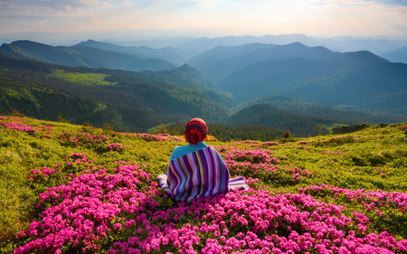 The girl in striped plaid is sitting on the lawn among pink rhododendrons watching at the mountains landscapes and sun.