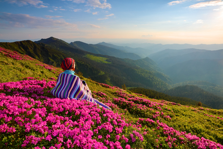 The girl sits on the lawn covered with pink flowers watching at the high mountains, sky with clouds and sun in summer day.