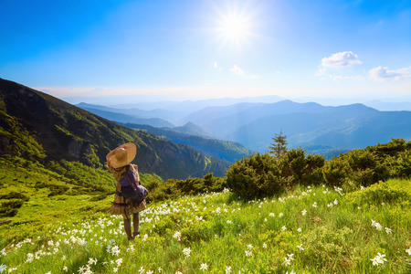 The lawn with white daffodils in the high mountains landscapes. The girl in overknees stockings, romantic dress, back sack and straw hat. Unbelievable summer landscape.