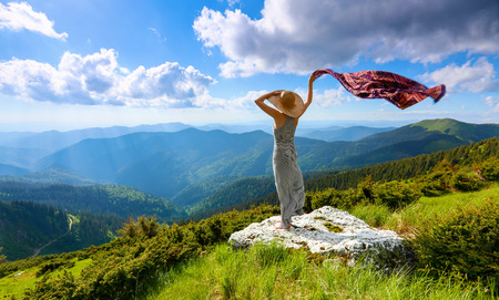On the white rocks at the lawn the girl in long dress and hat is staying with the shawl in hand watching at the blue sky and mountains. Nice view for nature lovers. Summer  landscape.