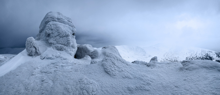 At the high mountains there are fantastic, interesting, frozen structured rocks looking like mystical fairytale figures. The panoramic view with the fog, high peaks in snow, adventure mood in the winter day. Stock Photo